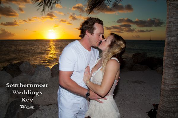 Couple kissing with the sunset in the background - Image by Southernmost Weddings