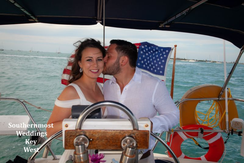 Wedding couple steering the sailboat after their wedding by Southernmost Weddings Key West