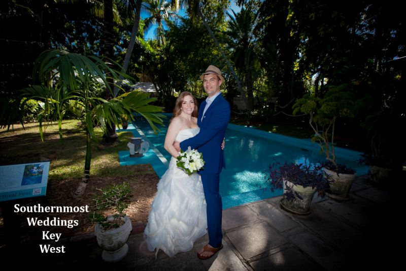 Wedding couple poses for photos infront of the pool on the grounds of the Hemingway House & Museum