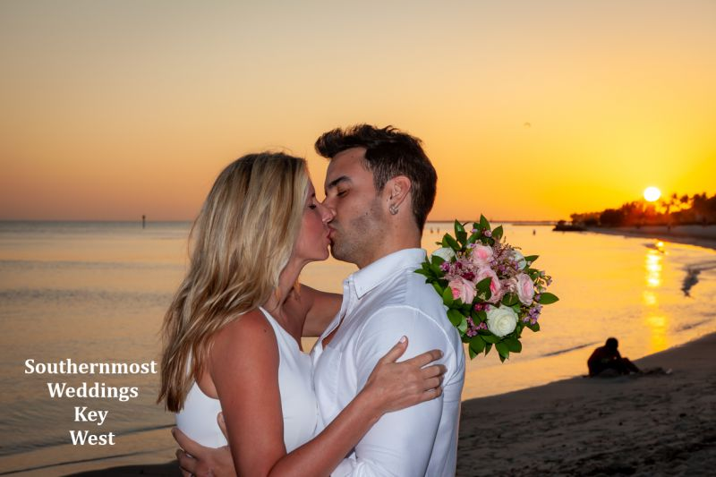 Wedding Couple kisses on the beach with the sun setting in the background by Southernmost Weddings