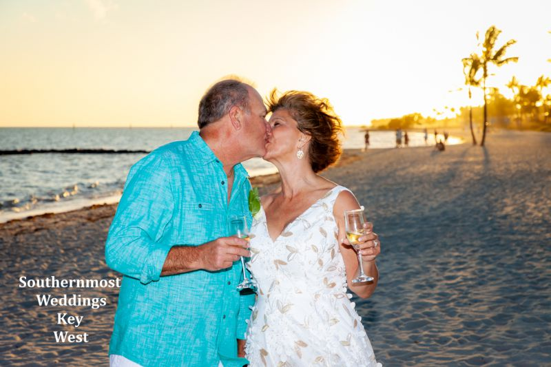 Wedding couple kisses on Smathers Beach after their wedding by Southernmost Weddings Key West