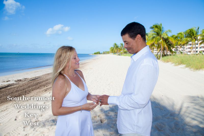 Wedding couple exchange rings during their ceremony on Smathers Beach in Key West, Florida