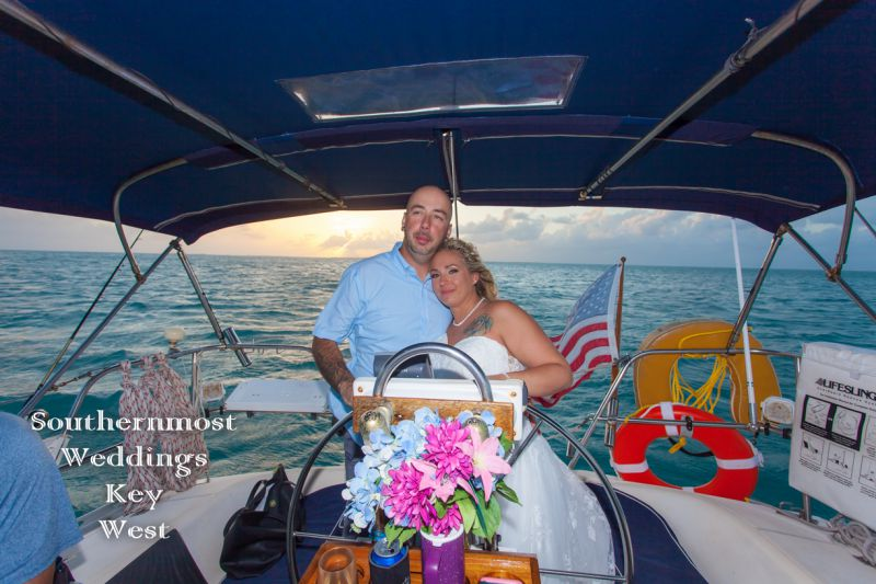 Wedding couple steering the sailboat after their wedding by Southernmost Weddings