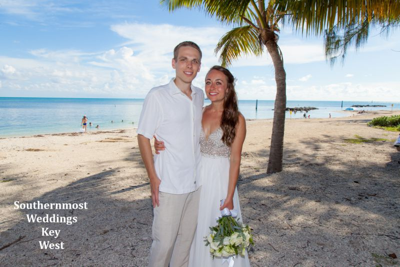 Wedding couple stand under a palm tree next to the ocean at Ft. Zachary Taylor State Park in Key West, Florida